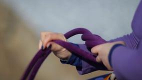 Plan rapproché de la main d'une femme attachant un noeud s'élevant banque de vidéos