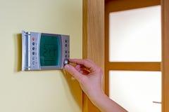 Plan rapproché de la main d'une femme plaçant la température ambiante sur un mode Image libre de droits