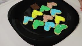 Plan rapproché de la main d'une fille, un enfant, arrosant les biscuits délicieux de sucrerie douce pliés sous forme d'arbre de N banque de vidéos