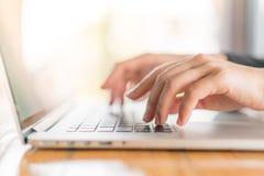 Plan rapproché de la main de femme d'affaires dactylographiant sur le clavier d'ordinateur portable photos stock