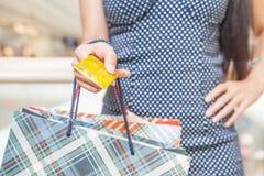 Plan rapproché de la main de la femme tenant la carte de crédit et les sacs Photographie stock libre de droits