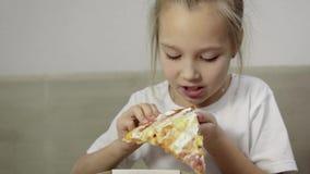 Plan rapproché de la main du bébé prenant un morceau de pizza juteuse et grasse et l'apportant à sa bouche, fille drôle dans le T clips vidéos