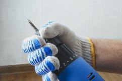 Plan rapproché de la main masculine avec le tournevis bleu contre le mur et le plancher blancs image stock