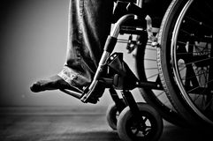 Plan rapproché de la main masculine sur la roue du fauteuil roulant Image stock