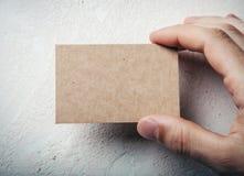 Plan rapproché de la main masculine tenant la carte d'entreprise artisanale images stock