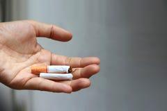 Plan rapproché de la main masculine tenant la cigarette cassée sur la paume Photographie stock libre de droits