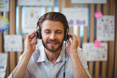 Plan rapproché de la musique de écoute masculine de concepteur sur l'écouteur Photos stock