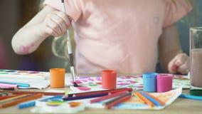 Plan rapproché de la peinture femelle caucasienne d'enfant avec des aquarelles une photo au club d'art banque de vidéos