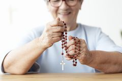 Plan rapproché de la personne âgée de sourire tenant le chapelet avec la croix photos stock