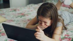 Plan rapproché de la petite fille mignonne à l'aide du comprimé numérique et souriant tout en se trouvant dans le lit Film wathci banque de vidéos