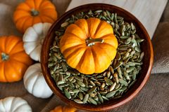 Plan rapproché de la pleine cuvette de graines de citrouille épluchées avec le potiron orange, Autumn Holidays Image stock