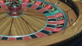 Plan rapproché de la roue de roulette en bois tournant dans le premier plan Tableau dans le casino de luxe banque de vidéos