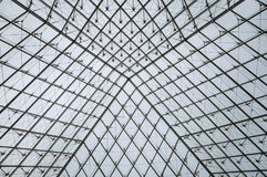 Plan rapproché de la structure en verre et en acier de plafond sur le musée de Louvre dans un jour nuageux à Paris Photos stock