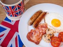 Plan rapproché de lard et d'oeufs avec la tasse du thé et du drapeau des anglais Photo stock