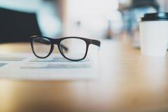Plan rapproché de lieu de travail confortable dans le bureau avec la table et les verres en bois là-dessus Foyer sélectif Fonctio Photo stock