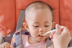 Plan rapproché de mère alimentant le bébé asiatique avec une cuillère dans haut c images stock