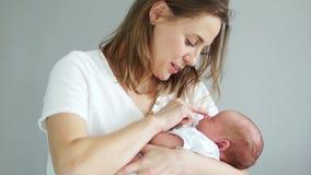 Plan rapproché de mère de bonheur tenant le bébé nouveau-né sur ses bras Maternité heureuse, mère et enfant, bébé de sommeil banque de vidéos