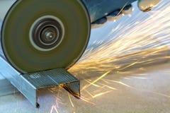 Plan rapproché de métal de coupe de travailleur avec la broyeur Étincelle tandis que grimace image libre de droits