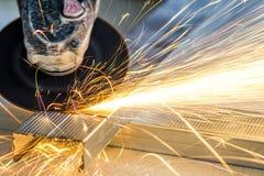 Plan rapproché de métal de coupe de travailleur avec la broyeur Étincelle tandis que grimace images stock