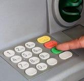 Plan rapproché de main écrivant le code de PIN/pass sur le keyp de machine d'ATM/bank Image libre de droits