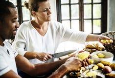 Plan rapproché de main avec la peau de pomme de terre d'épluchage de couteau Images stock