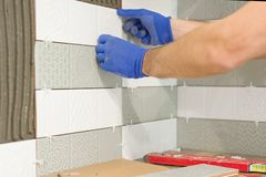Plan rapproché de main de carreleur étendant le carreau de céramique sur le mur dans la cuisine, rénovation, réparation, construc images stock