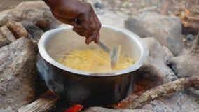 Plan rapproché de main d'Afro-américain avec des pâtes de mélange de cuillère dans un pot sur le feu clips vidéos