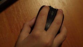 Plan rapproché de main d'enfant utilisant l'ordinateur de souris sur la table en bois banque de vidéos