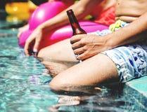 Plan rapproché de main de l'homme tenant la bouteille à bière par le poolside Photos stock