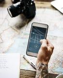 Plan rapproché de main de tatouage tenant le téléphone portable montrant à généralistes l'itinéraire image stock