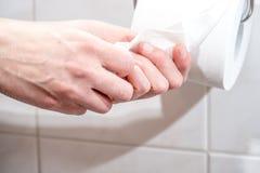 Plan rapproché de main du ` s de dame d'A utilisant le papier hygiénique photo stock