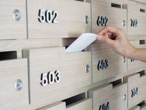 Plan rapproché de main du ` s de personne remettez enlever une lettre de la boîte aux lettres dans le hall d'entrée d'un immeuble Photo libre de droits