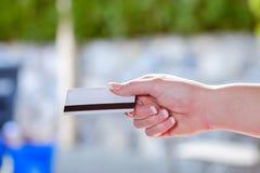 Plan rapproché de main femelle passant une carte de crédit Photos stock