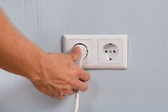 Plan rapproché de main insérant une prise électrique Photos libres de droits
