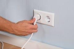 Plan rapproché de main insérant une prise électrique Images stock