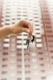 Plan rapproché de main tenant des clés contre le haut nouveau bâtiment Photo stock