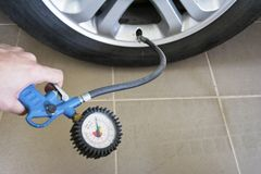Plan rapproché de main tenant l'indicateur de pression pour la mesure de pression de pneu de voiture photographie stock