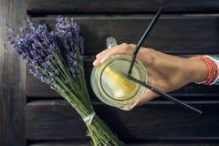 Plan rapproché de main tenant une tasse de limonade Photographie stock libre de droits