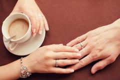 Plan rapproché de mains de couples de mariage et de tasse de café Photographie stock libre de droits