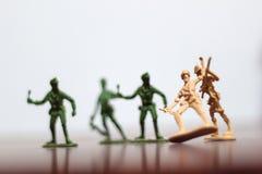 Plan rapproché de miniature par groupe de soldats de jouets de plastique à la guerre Photos stock
