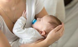 Plan rapproché de 3 mois mignons de bébé dormant sur des mains de mères Images stock