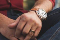 Plan rapproché de montre-bracelet sur le bras d'un jeune homme dehors dans les vêtements décontractés photographie stock