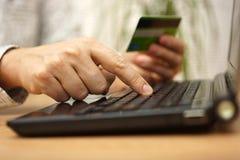 Plan rapproché de numéro de carte entrant de crédit de jeune sur l'ordinateur portable c Images stock