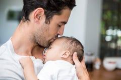 Plan rapproché de père embrassant le bébé tout en se tenant Photographie stock libre de droits