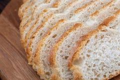 Plan rapproché de pain coupé en tranches Regard rustique sur le fond de conseil en bois photographie stock libre de droits