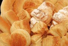 Plan rapproché de pain et de pâtisserie d'isolement sur le noir Photographie stock libre de droits