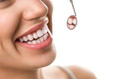 Plan rapproché de patient de sourire avec la dent saine avec le miroir dentaire photographie stock