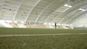 Plan rapproché de pelouse dans le stade avec les athlètes s'exerçants action Stade d'intérieur avec l'herbe verte et les joueurs  photographie stock