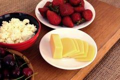 Plan rapproché de petit déjeuner sain : fromage blanc, fraises, cerise et fromage coupé en tranches sur le conseil en bois Rétro  photographie stock