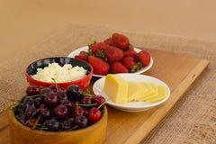 Plan rapproché de petit déjeuner sain : fromage blanc, fraises, cerise et fromage coupé en tranches sur le conseil en bois Rétro  images libres de droits